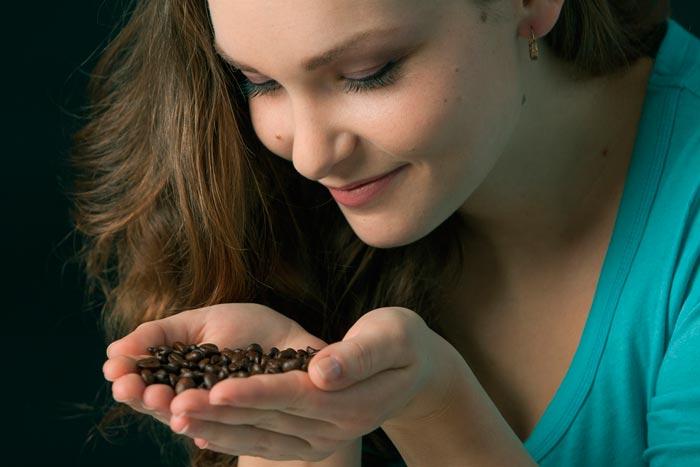 нюхает зерна кофе
