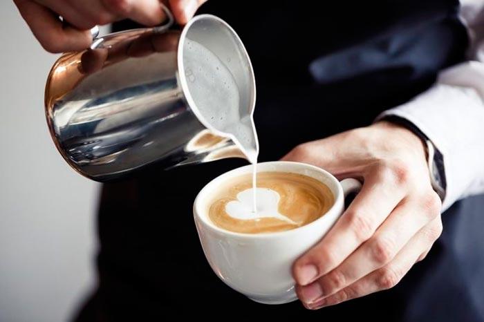 наливает сливки в кофе